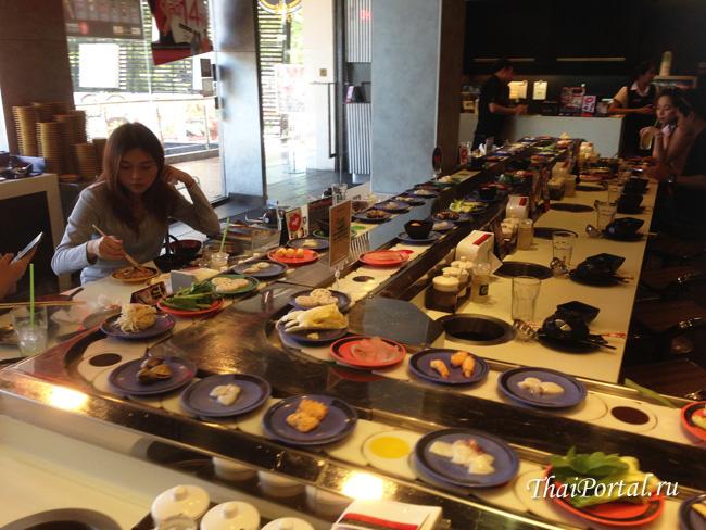 молодая таечка кушает палочками в ресторане Шабуши в Бангкоке
