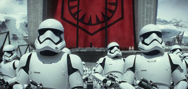 Кадр из фильма «Звёздные войны: Пробуждение силы» (Star Wars: The Force Awakens) космической саги Звёздные Воины, на котором изображаются имперские штурмовики, облаченные в белую броню с лазерами наготове.