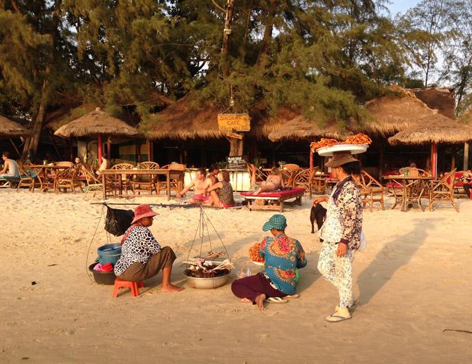 торговки-кхмерки продают туристам на пляже Otres в Сиануквиле запеченных на углях лобстеров и другие морепродукты, выловленные в Сиамском заливе