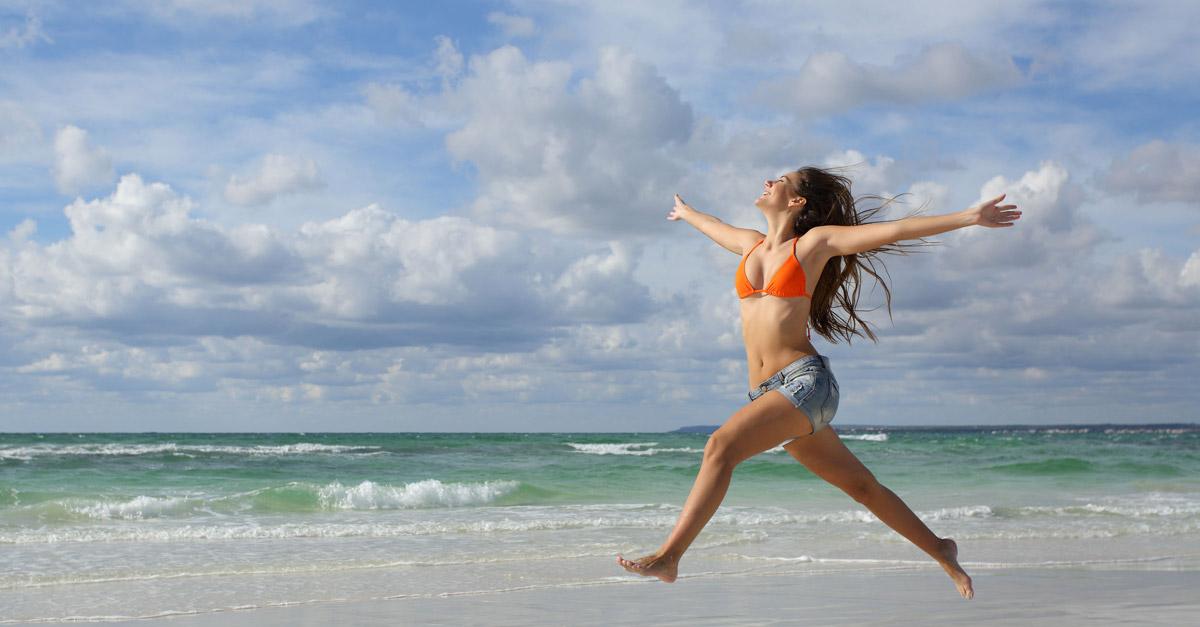 радостная девушка без признаков ожирения бежит по пляжу вдоль моря на фоне волн