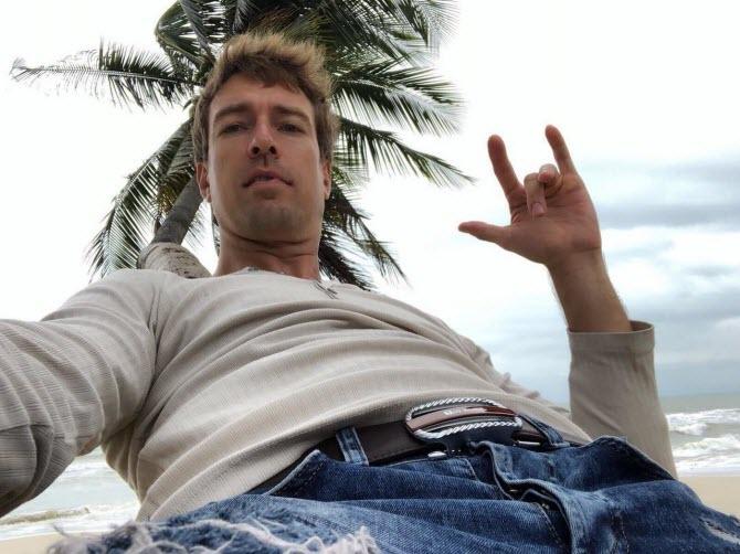 Алекс Лесли позирует на фоне пальмы и моря