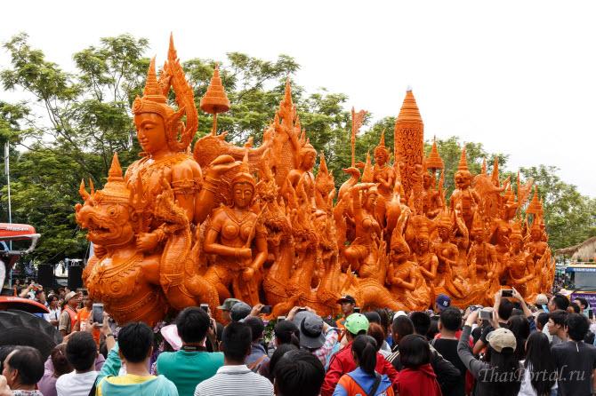 процессия с гигантской скульптурной композицией из воска, созданной тайскими мастерами, двигается во время фестиваля свечей в городе Убонратчатхани