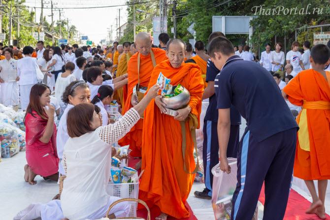 типичная сцена на улицах тайских городов - монахи принимают подношения во время буддийского праздника