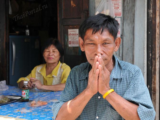демографические проблемы Таиланда - тайский старик приветствует прохожих жестом вай