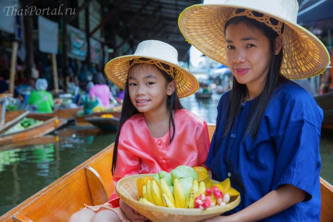 тайские мать и дочь покупают фрукты на плавучем рынке в Таиланде