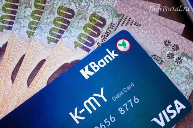 эмитированные тайским банком Kasikorn дебетовые карты с магнитной полосой и стопка купюр в тысячу тайских бат