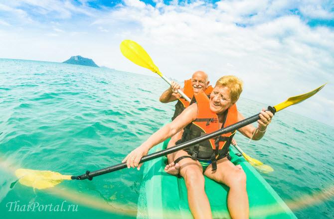 западные пенсионеры радостно гребут веслами, катаясь на каяке по морю в Таиланде