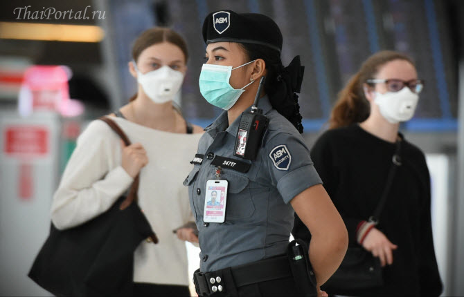сотрудница тайского аэропорта в форме и в маске для защиты от коронавируса