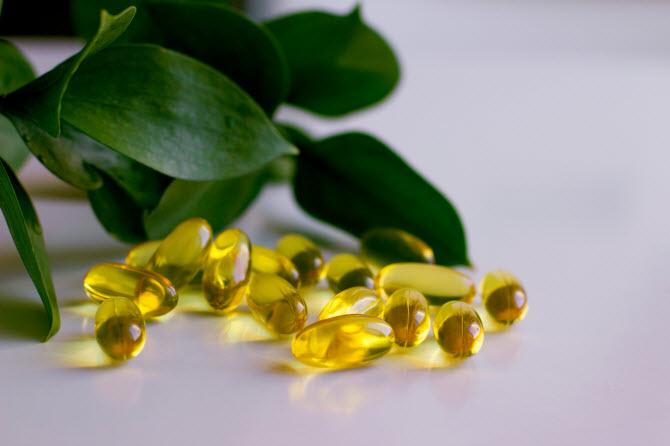 желтые прозрачные капсулы омега 3 на фоне зеленых листьев, символизирующих здоровье и жизнь